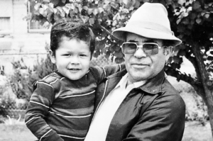 Image of a latino Mozilla employee as a child in the arms of his grandfather