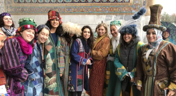 Kathy with a group of Uzbek women wearing traditional colourful clothing
