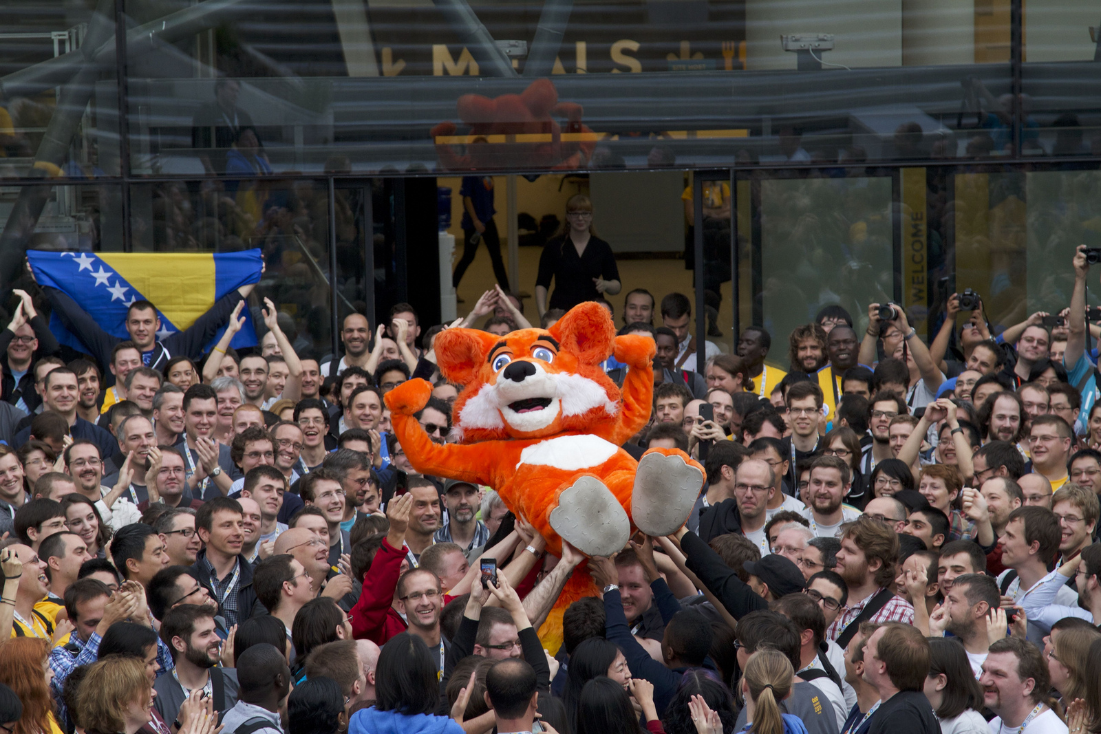 "The ""Foxy"" mascot is held aloft by attendees of the Mozilla 2013 Summit in Brussels"
