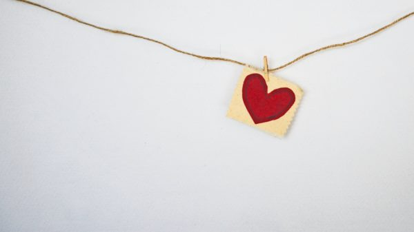 Paper, red heart hanging on a string with white background