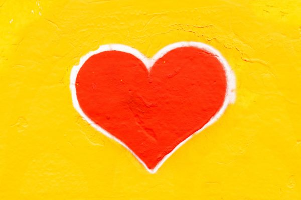 A Red heart, outlined in white on a yello background