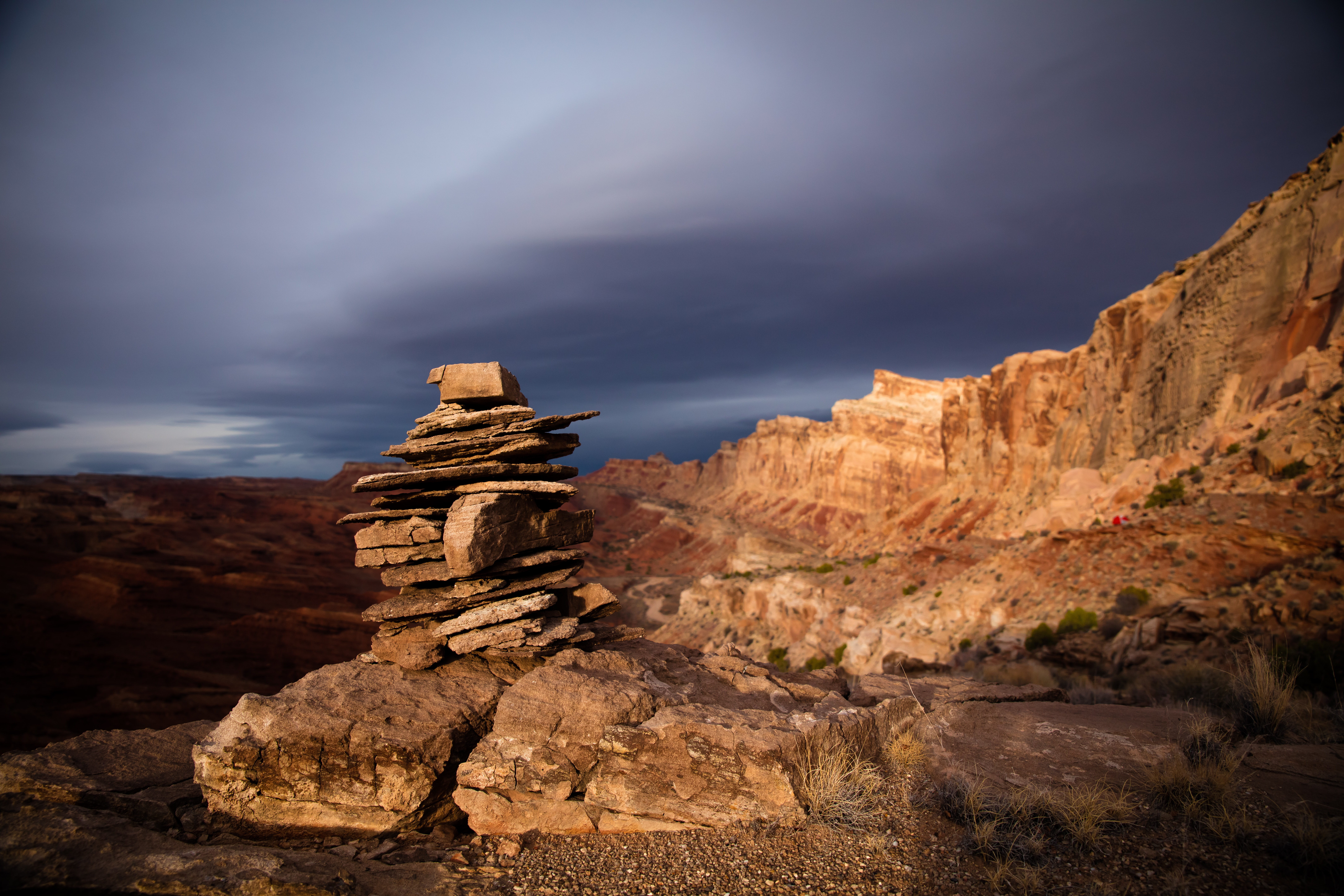 A stacked group of stones sits atop a mountain background
