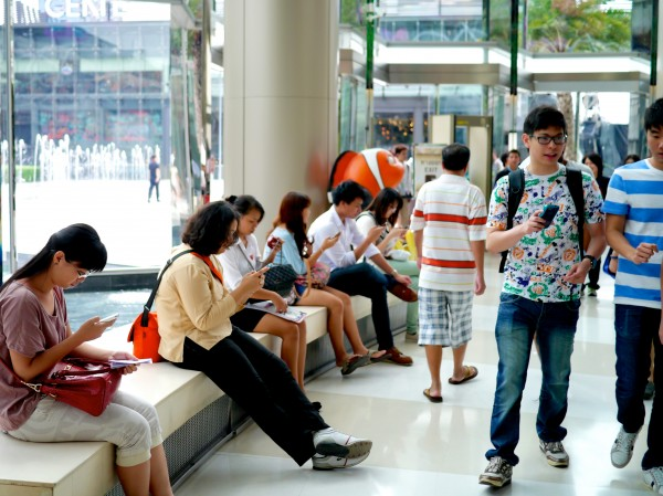 People using their mobile devices in a popular Bangkok mall.