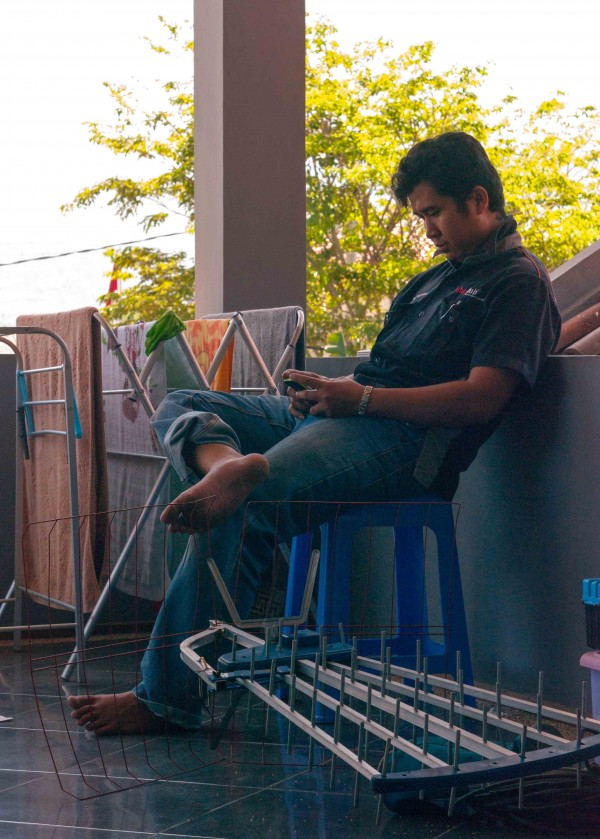 Air Conditioning Repairman Taking a Break with his Smartphone