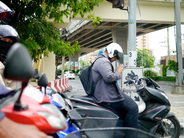 A man in Bangkok using his mobile device in traffic.