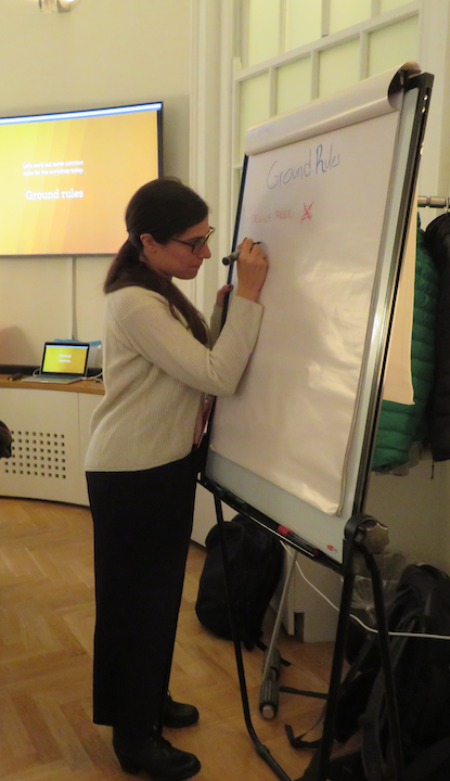 A photo of Emanuela, UX Designer and facilitator, scribing ground rules on a flip chart.