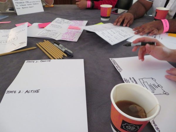 Image shows hands, paper, pencils, cups of coffee and tea.