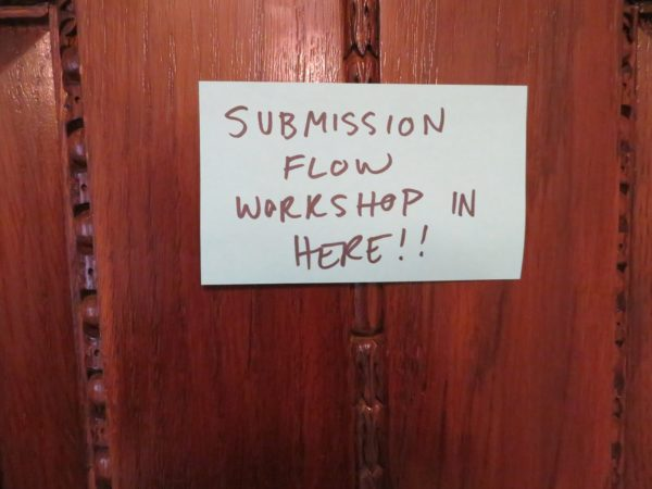 "Image: ""Submission flow workshop in here!!"" posted on a sticky note on a wooden door."