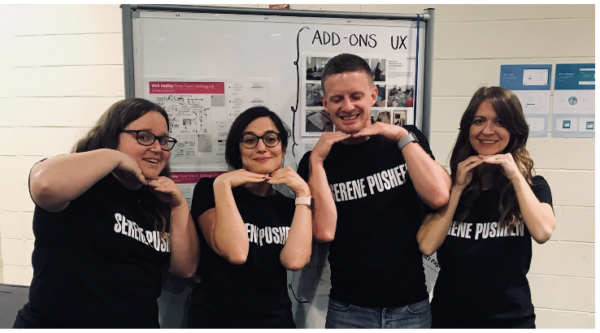 "Photo of the four team members, standing in a row. All four wear black t-shirts that read, ""Serene Pusheen."" They are smiling and have their hands under their chins."