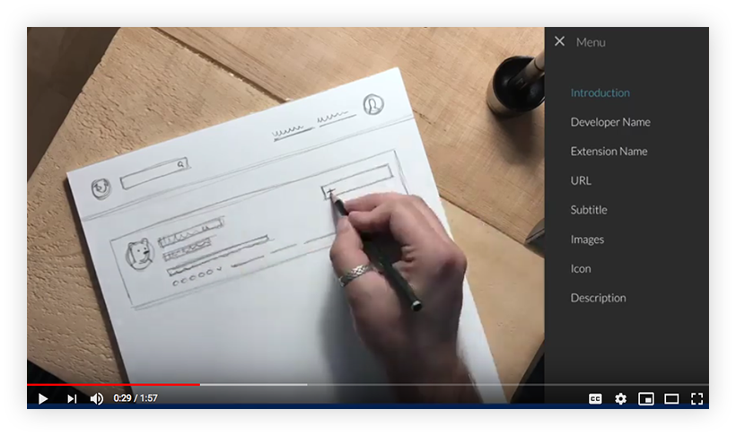 Screenshot of a video. A hand is sketching a rough product page on a piece of paper. Next to the paper is a table of content that includes an introduction and the main content elements on a product page, such as Developer Name, Extension Name, etcetera.