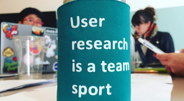 "A soda can in a coozy that says ""User research is a team sport,"" sitting on a table with people & laptops in the background."