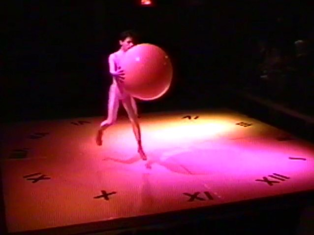 A man in a white leotard holding a large yoga ball on a small stage.